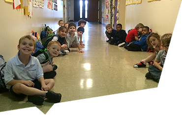 Children sitting in school hallway